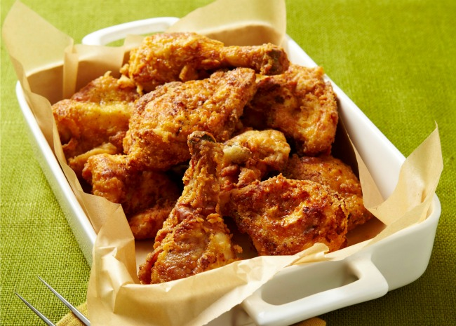 Fried Chicken in white pan with fork on napkin