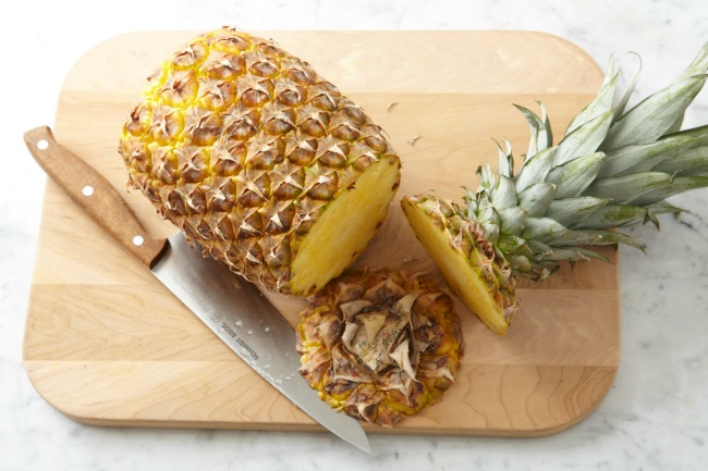 Topped pineapple on cutting board with knife