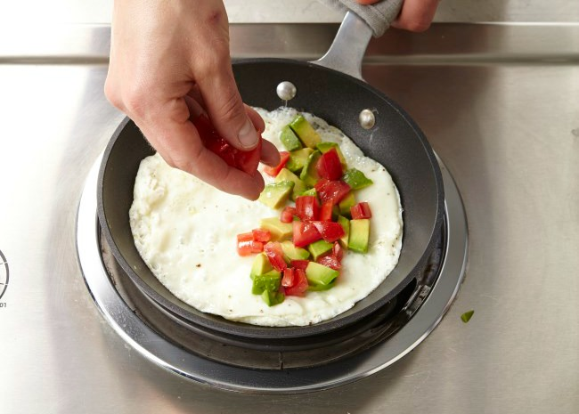 adding ingredients to one side of omelet