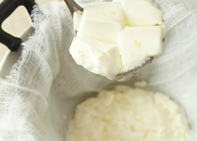 Slotted spooning mozzarella out of cheesecloth