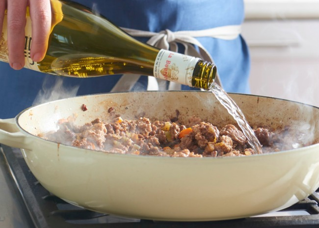 Pouring white wine into sauce