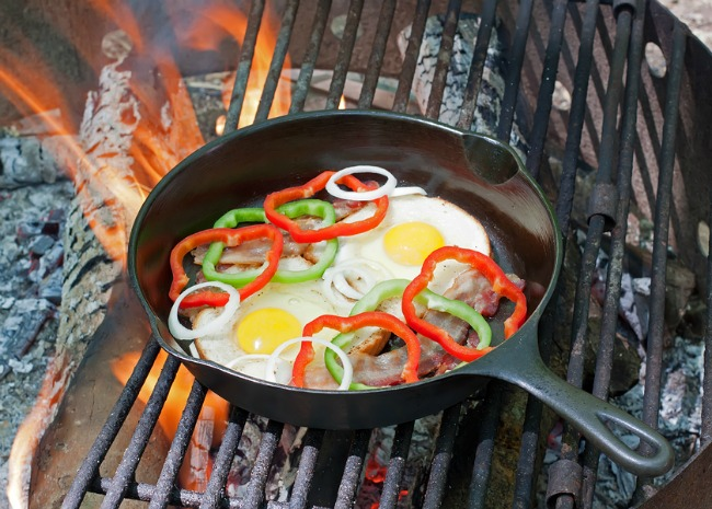 A breakfast of eggs on toast with bacononions and peppers frying on a grill.