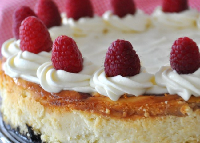 Cheesecake topped with raspberries and whipped cream
