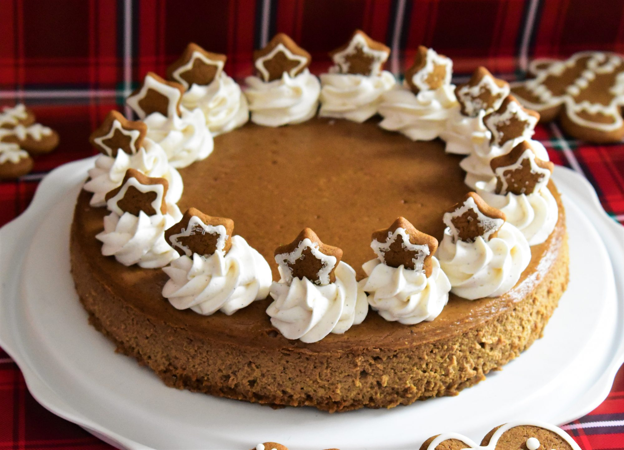 gingerbread cheesecake topped with whipped cream and cookies