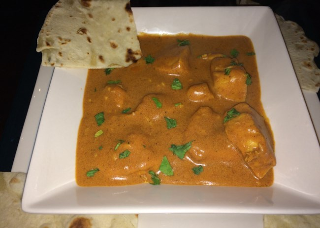 chicken tikka masala in a bowl with naan on the side