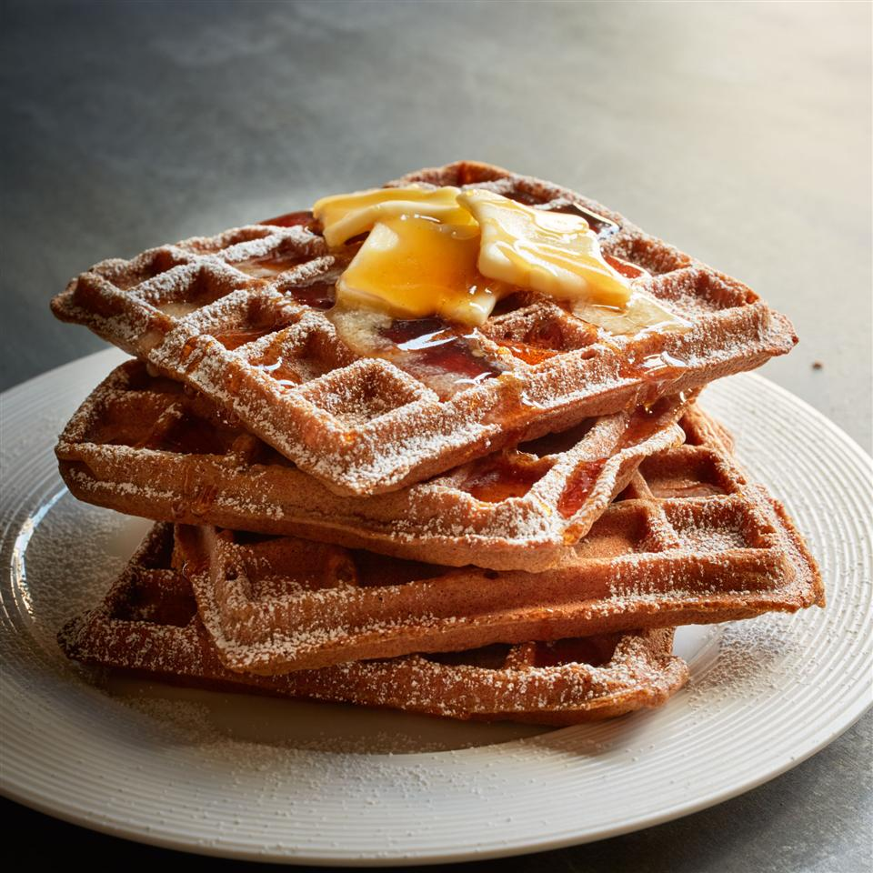 stack of gingerbread waffles with butter and syrup