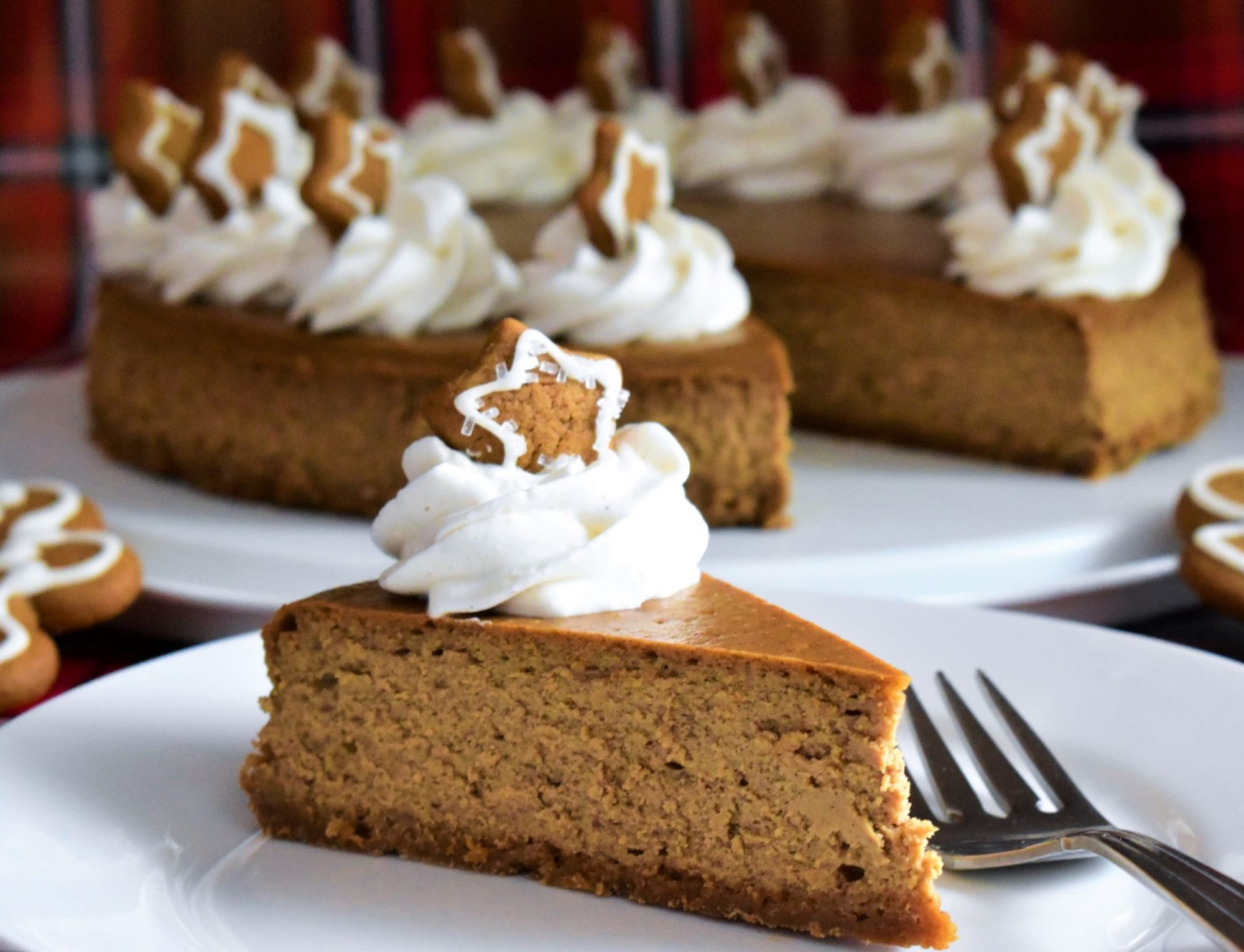 slice of gingerbread cheesecake topped with whipped cream and a gingerbread cookie