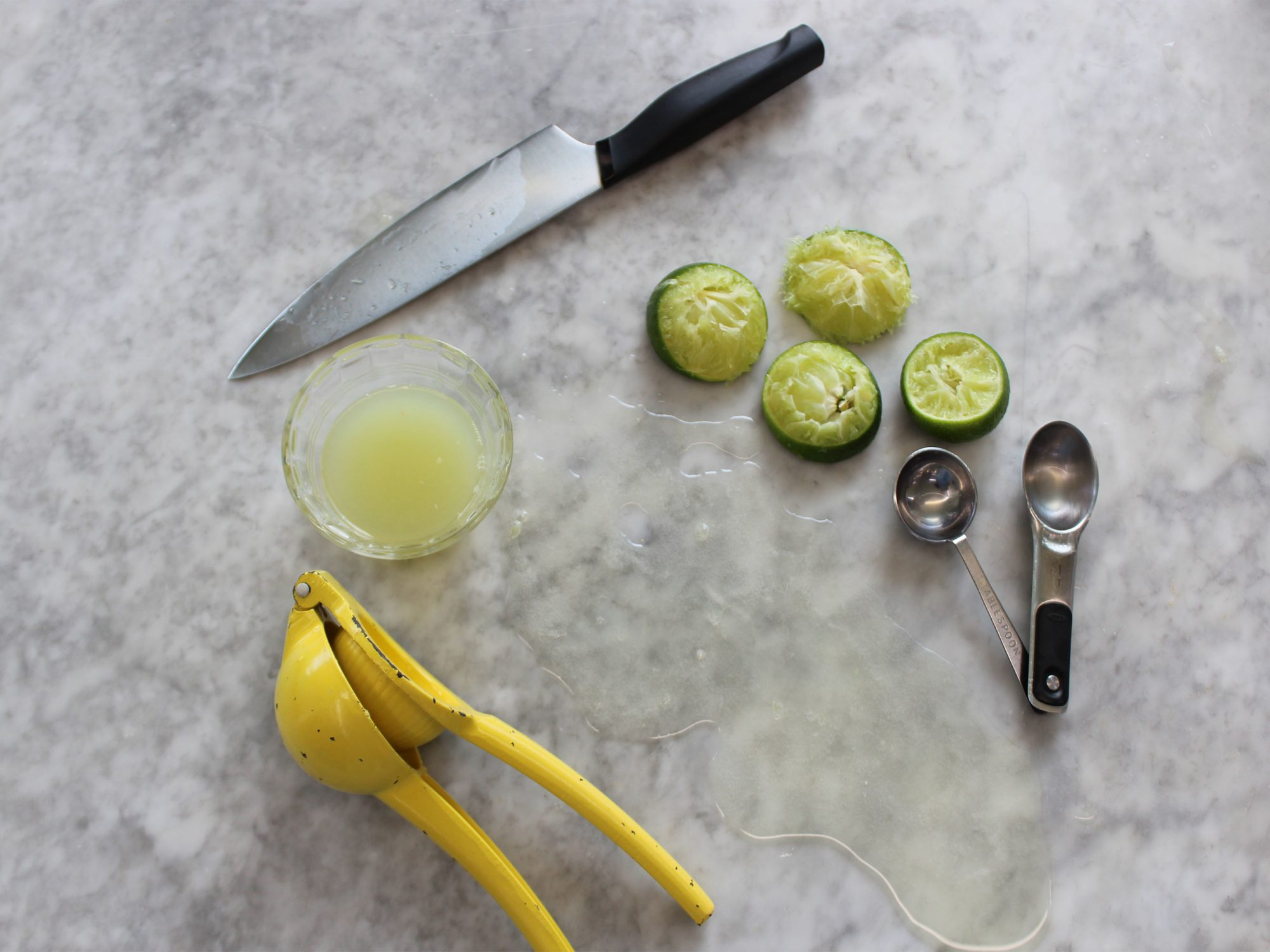 Limes, kitchen utensils, and spilled juice on countertop.