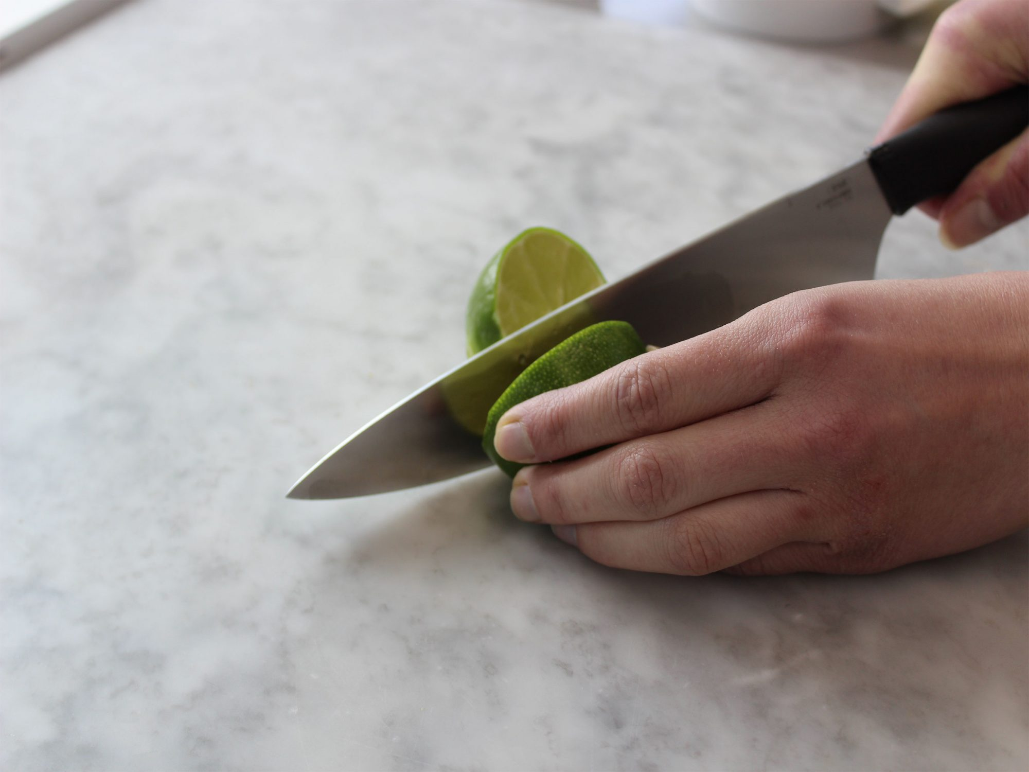 Lime sliced with knife on countertop