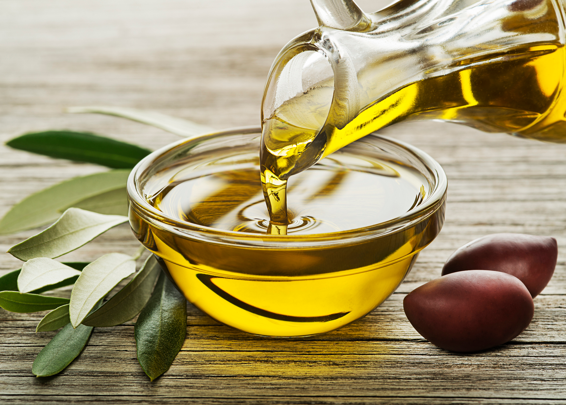 Bottle of Olive oil pouring close up