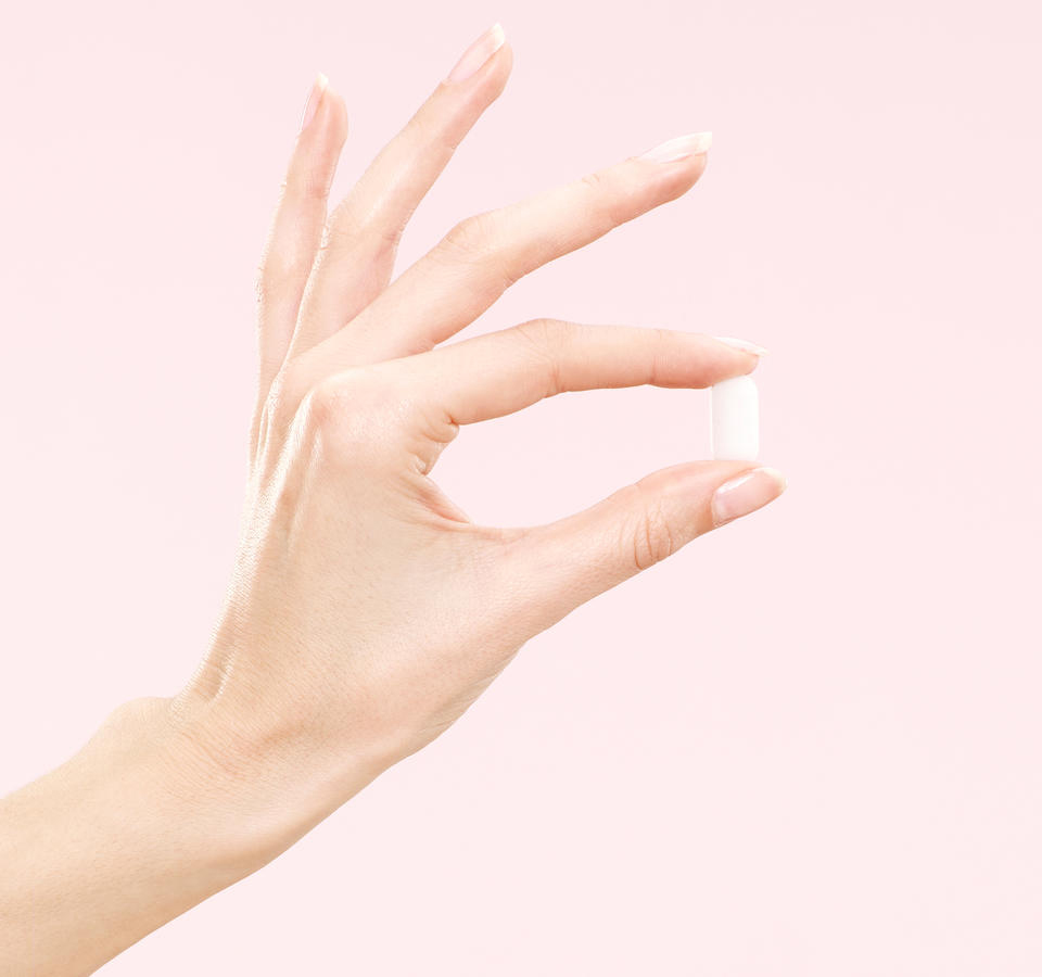 woman's thumb and index finger holding white pill with pink background