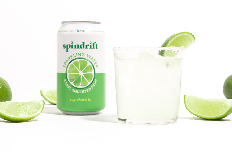 spindrift lime margarita in clear glass with can of sparkling lime on the side