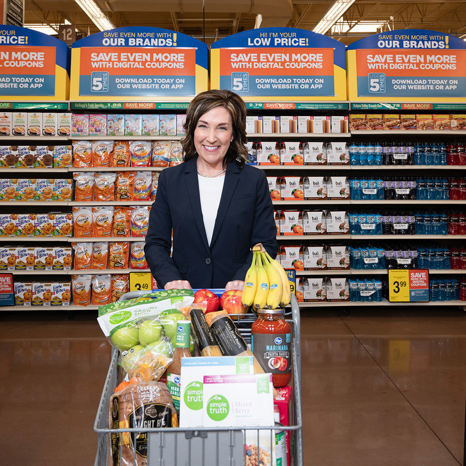 Woman in blue blazer holds grocery cart full of healthy foods in grocery aisle