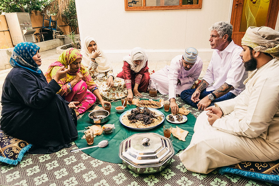Bourdain sitting to eat a meal with an Arab family in Oman