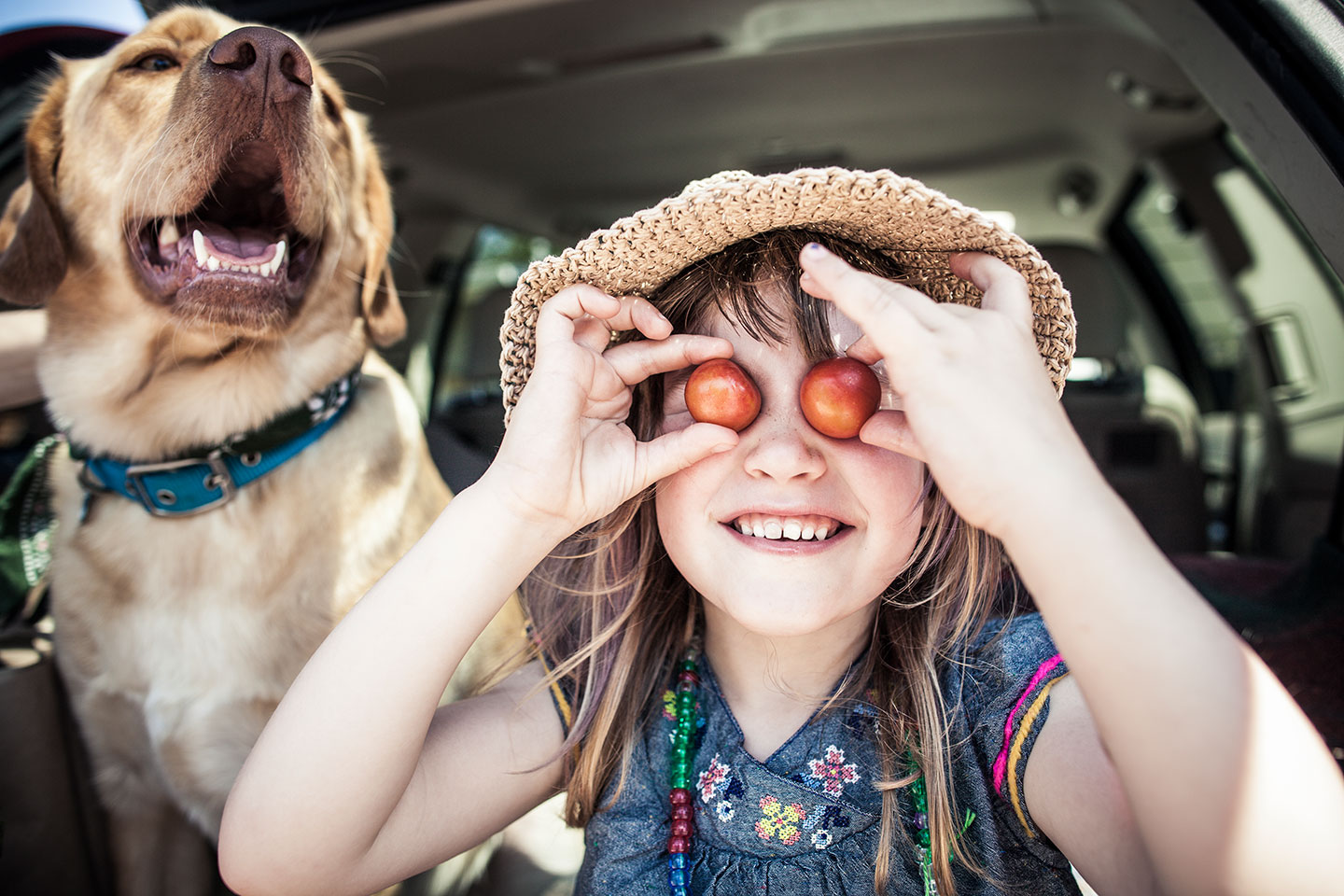 Girl and dog in the back of a car
