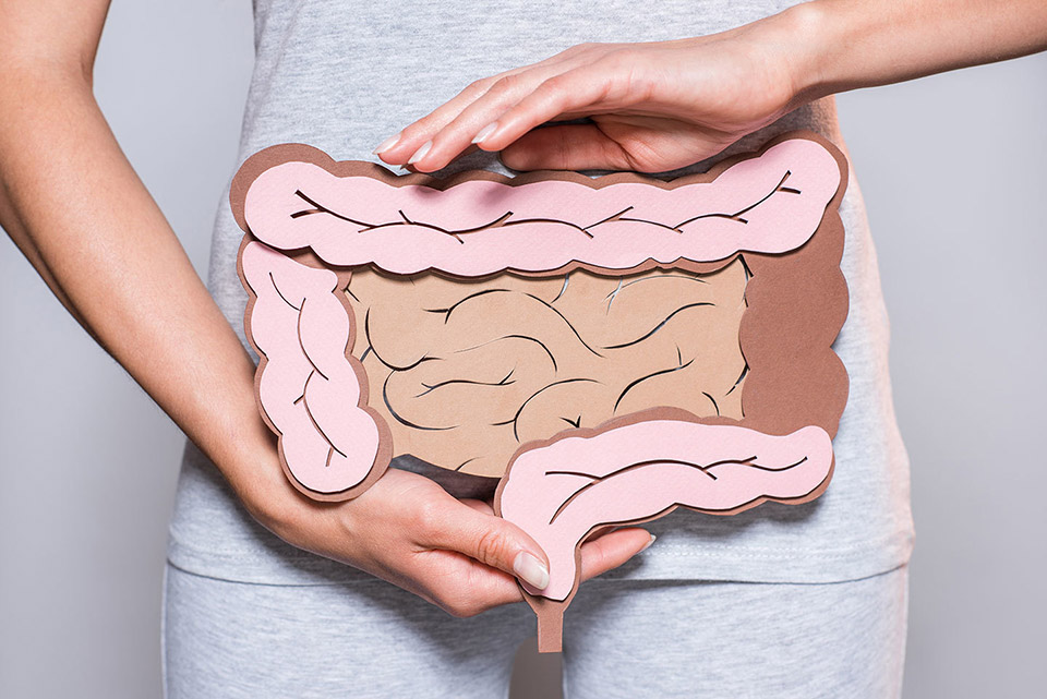woman holding paper intestines in front of her torso