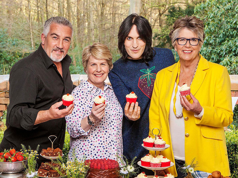 judges of The Great British Baking Show holding cupcakes and looking into the camera