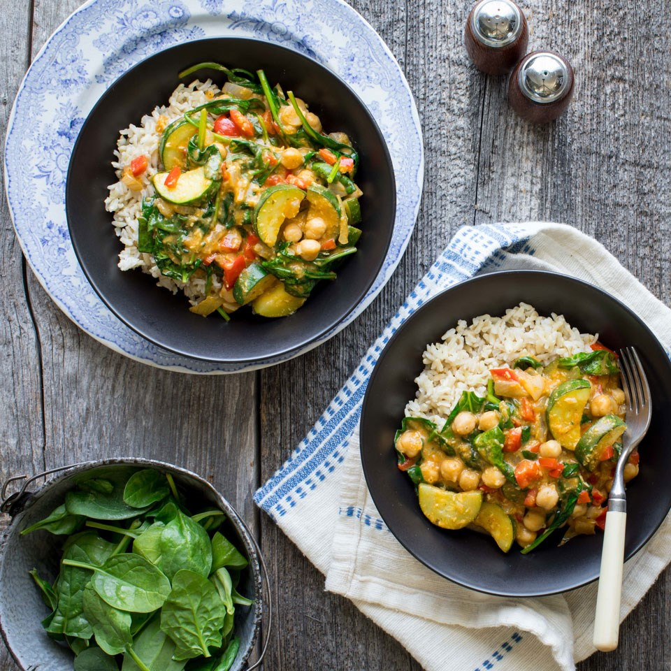 two bowls with veggie and rice meal and a bowl of raw baby spinach