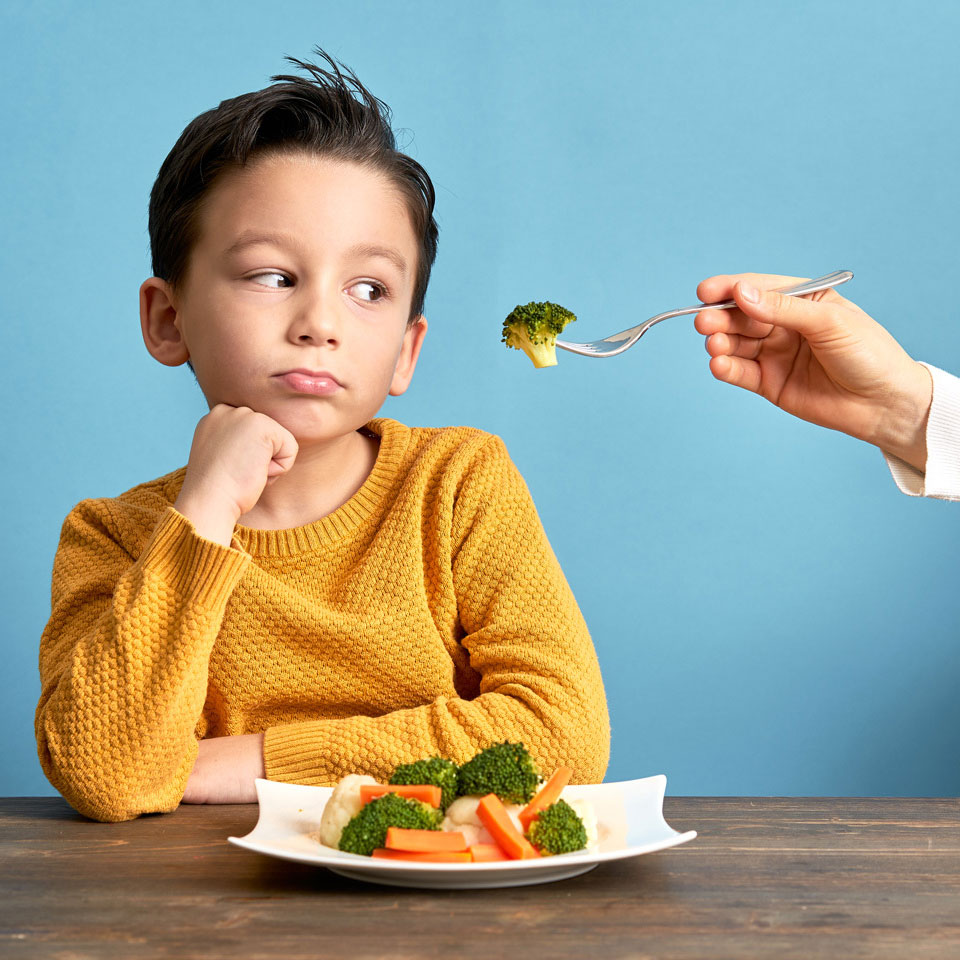 child looking suspiciously at an adult hand coming at their mouth with a fork with broccoli