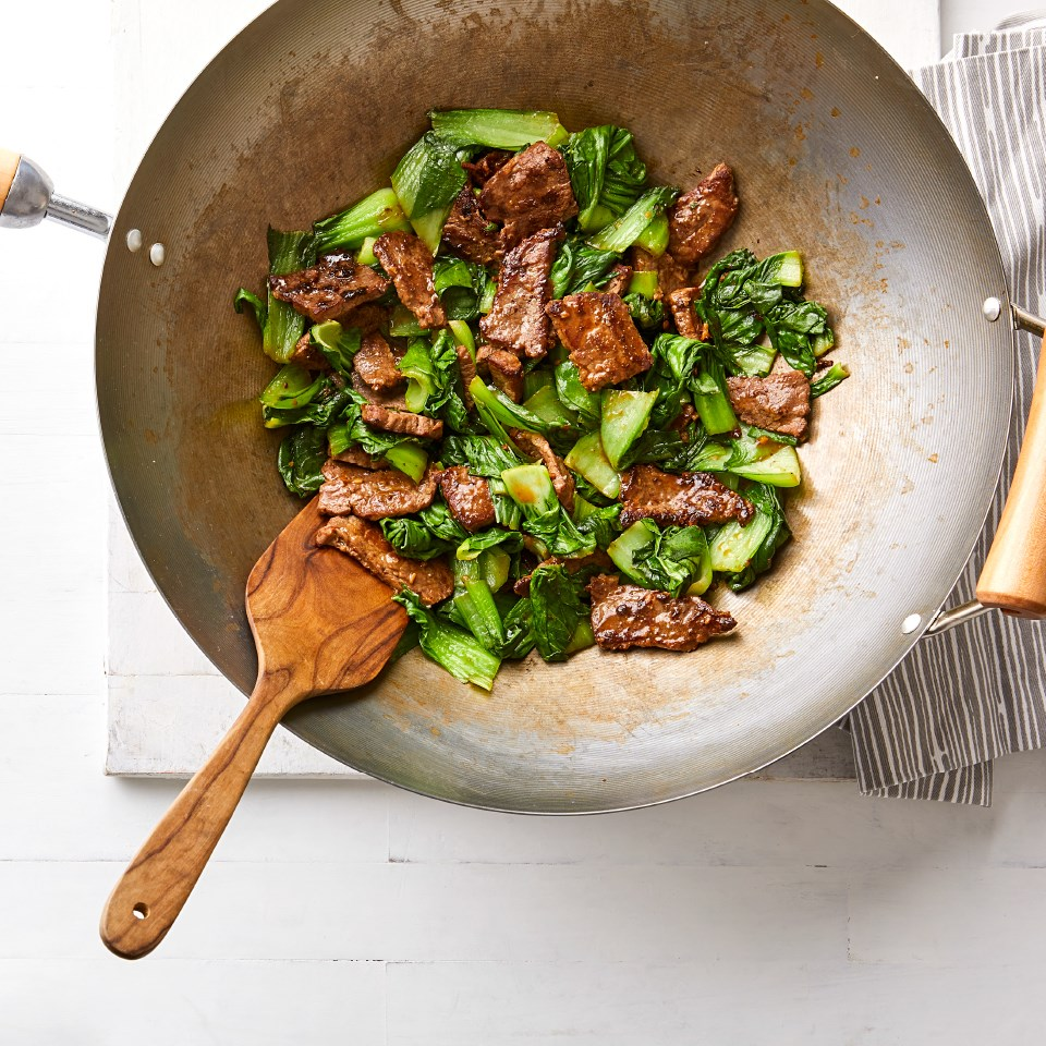 Chinese Ginger Beef Stir-Fry with Baby Bok Choy being cooked in a wok
