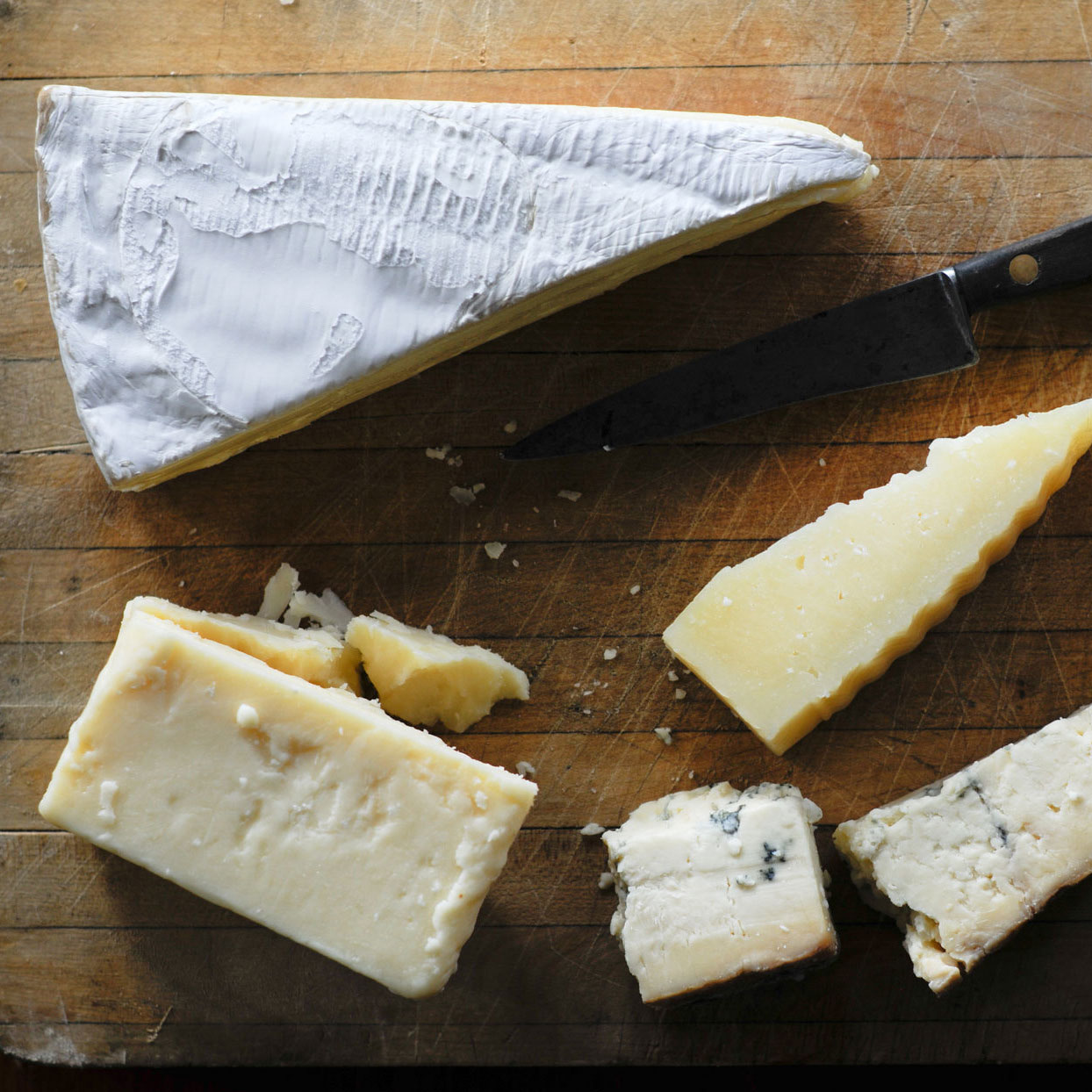 different types of cheeses on a board with a knife