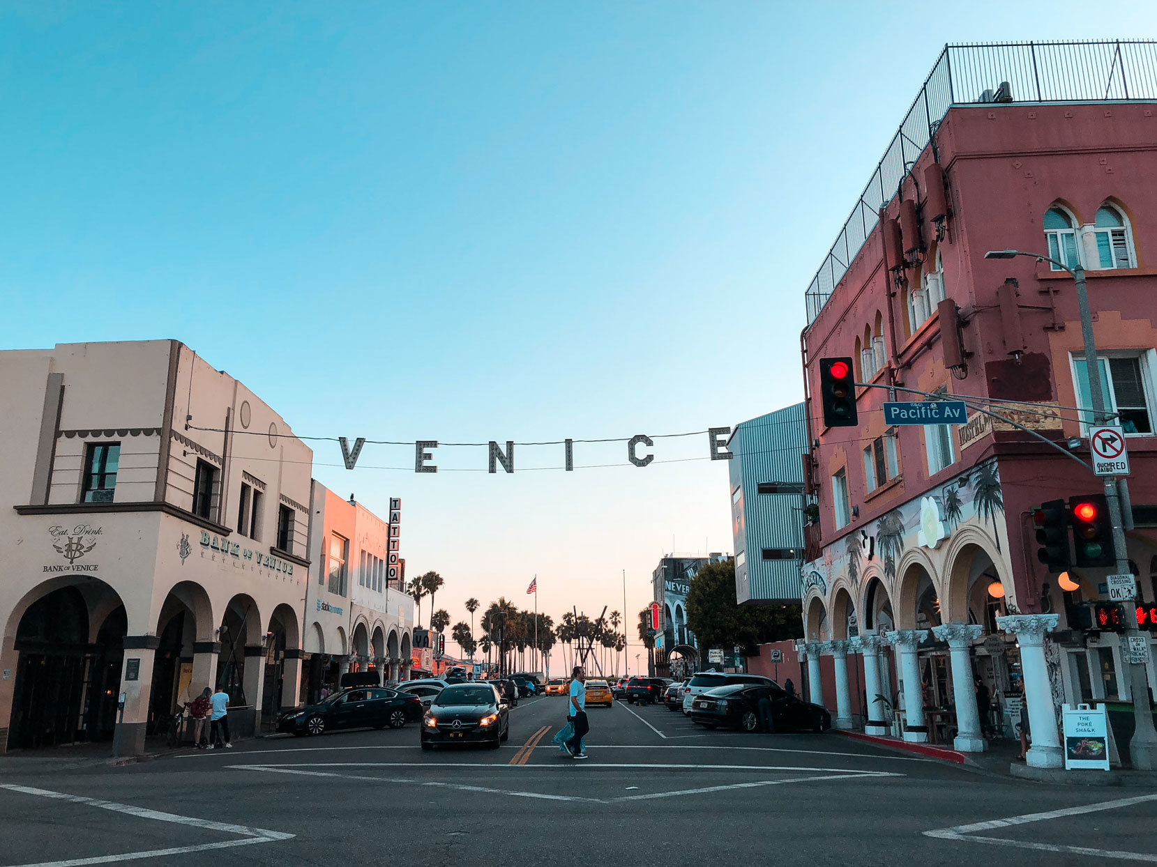 """City with palm trees in the distance and sign that says """"Venice"""" handing in between buildings in the foreground"""