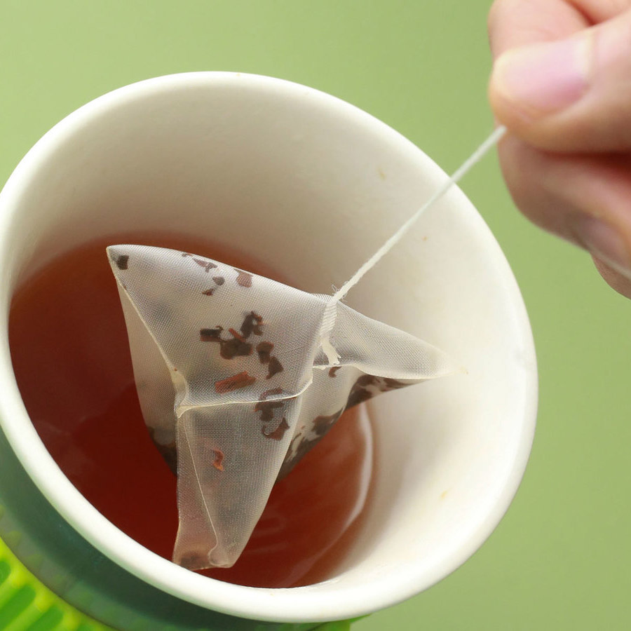 Plastic tea bag being dunked in a mug