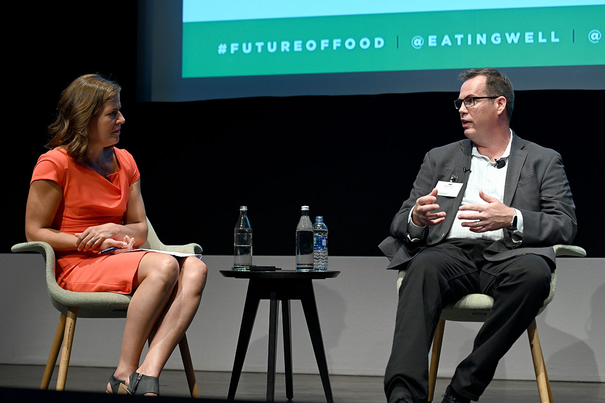 Jessie Price talks to GE's Chris Bissig on consumer technology in the kitchen, sitting on a stage with screen in background