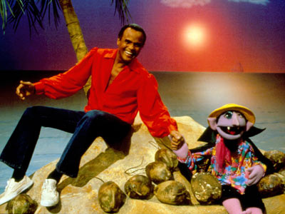 Harry Belafonte, Sesame Street | HARRY BELAFONTE Belafonte, sitting under a palm tree, sings a calypso-tinged ditty about a coconut-counting man, with two cute birdies as backup singers. We get…