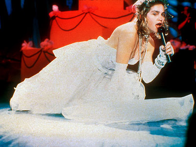 Madonna | Like a virgin? Not quite. When the burgeoning pop singer formerly known as Ms. Ciccone hit the stage in a lingerie-like wedding dress, fingerless gloves,…