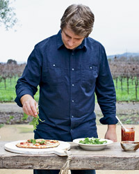 Kenny Rochford tops pizzas with arugula