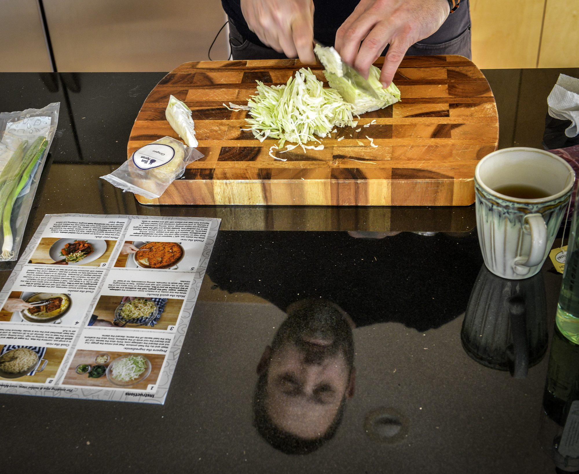 Chef Mike Isabella, reflected in his shiny black work surface, prepares a meal sent to him by Blue Apron