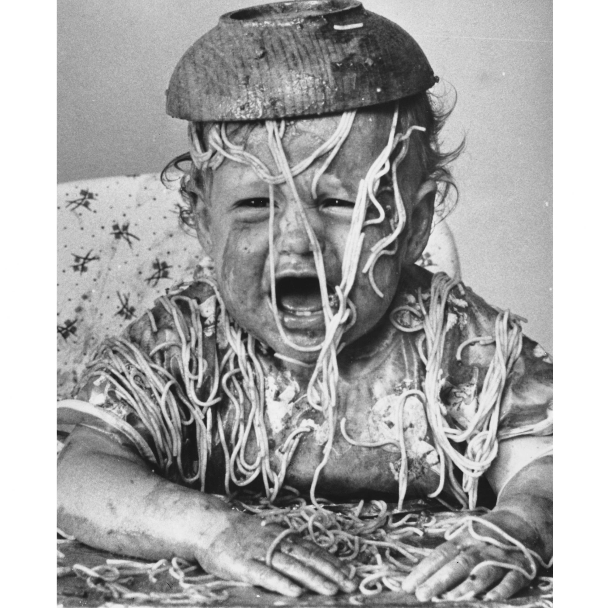 A child with a bowl of spaghetti on their head