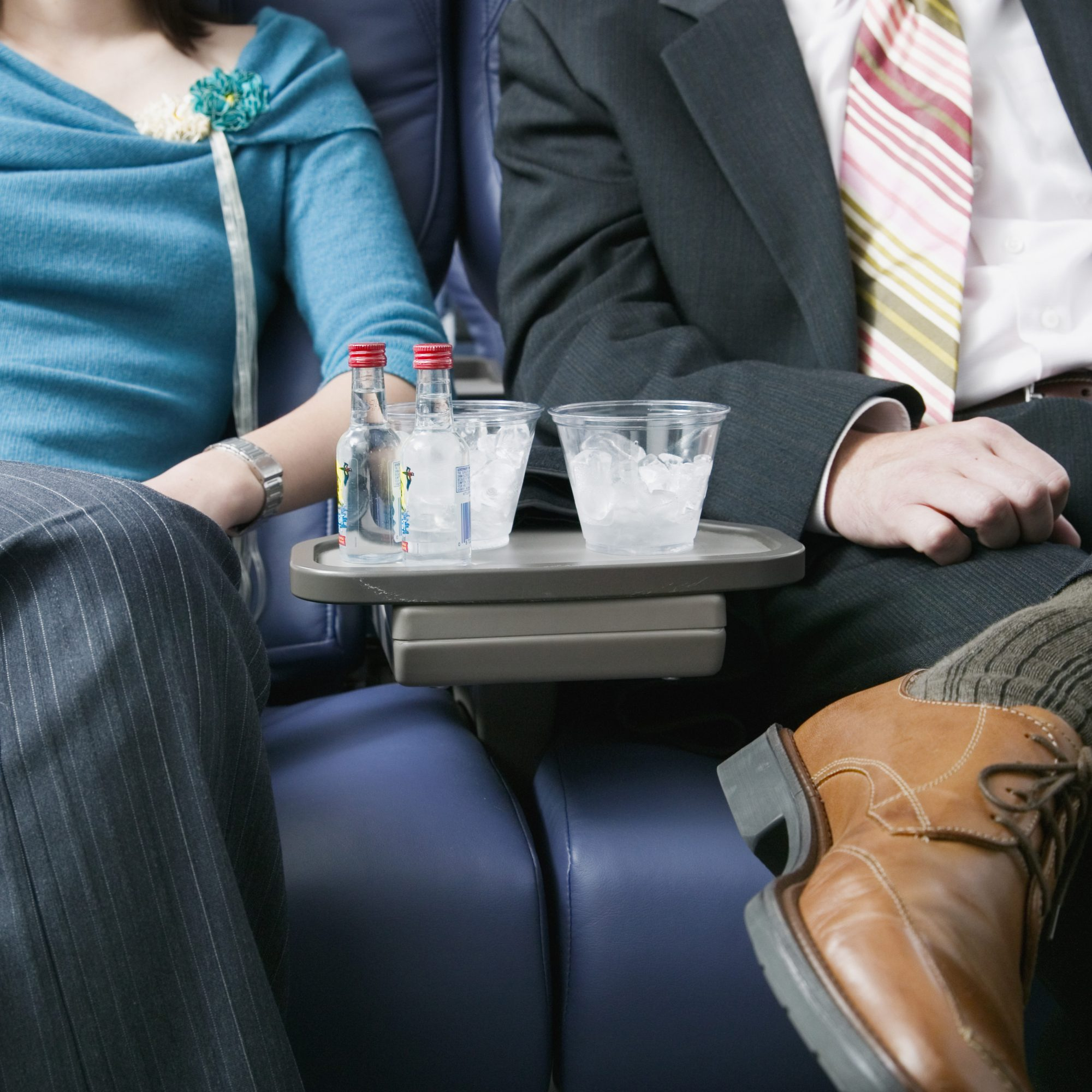 A couple drinks alcohol on a plane