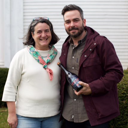 Eleanor Leger and Ryan Burk show off a bottle of their first co-produced cider.
