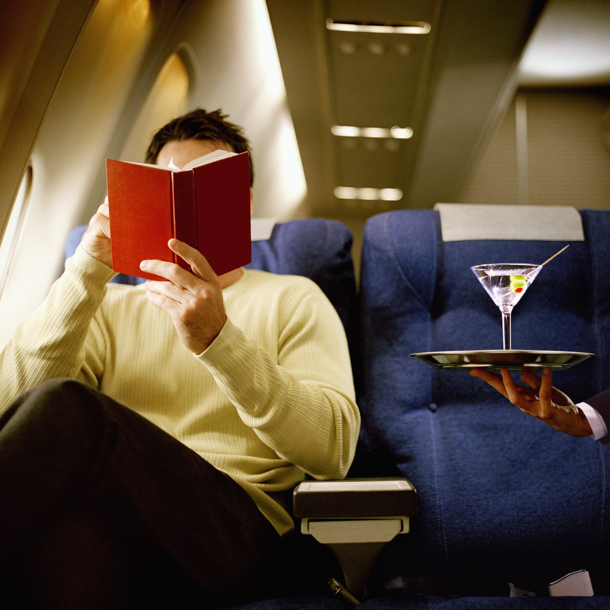 Man reading book, being served martini, in first class on airliner