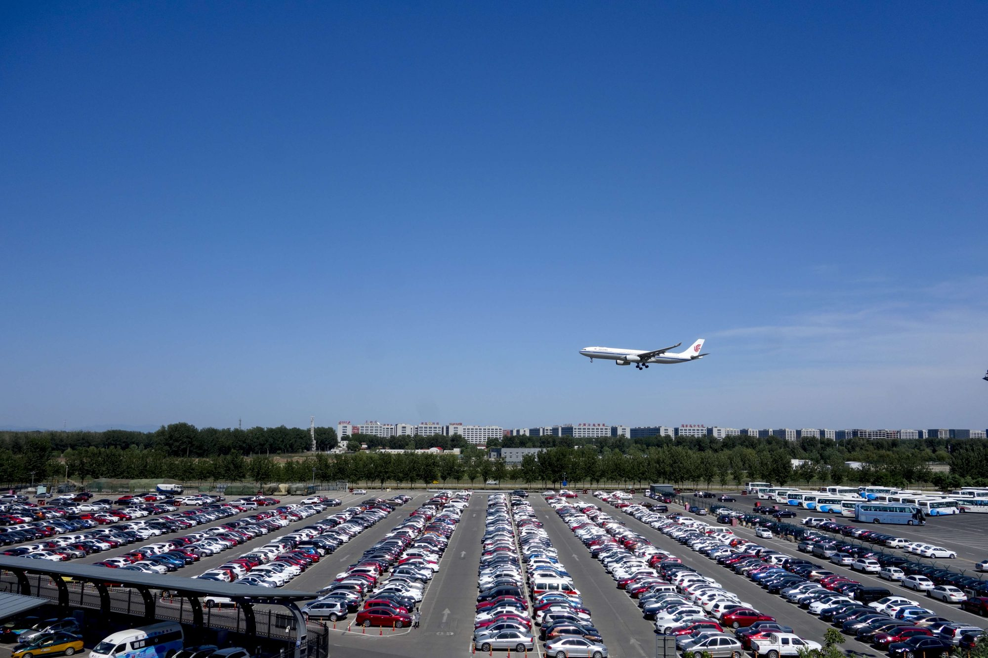 A plane of Air China flies over a parking lot as it cones in