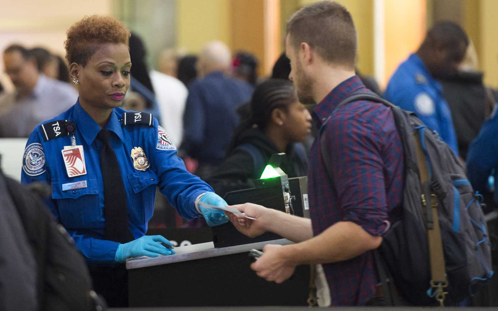 A TSA Agent checks the ID's of passengers as they pass through a security checkpoint on the way to their flights at Reagan National Airport