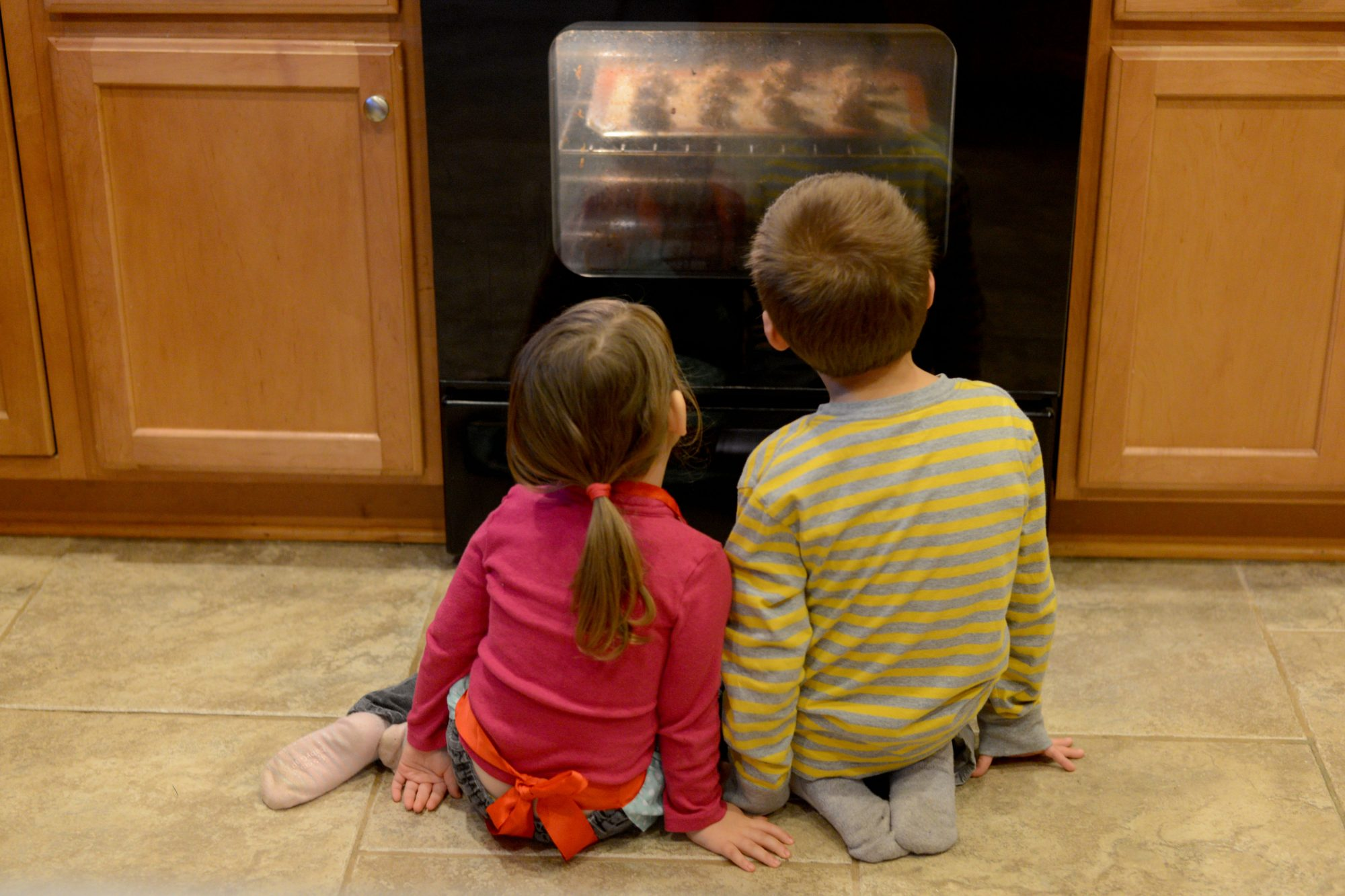Two Children Watching Cookies Rise in Oven