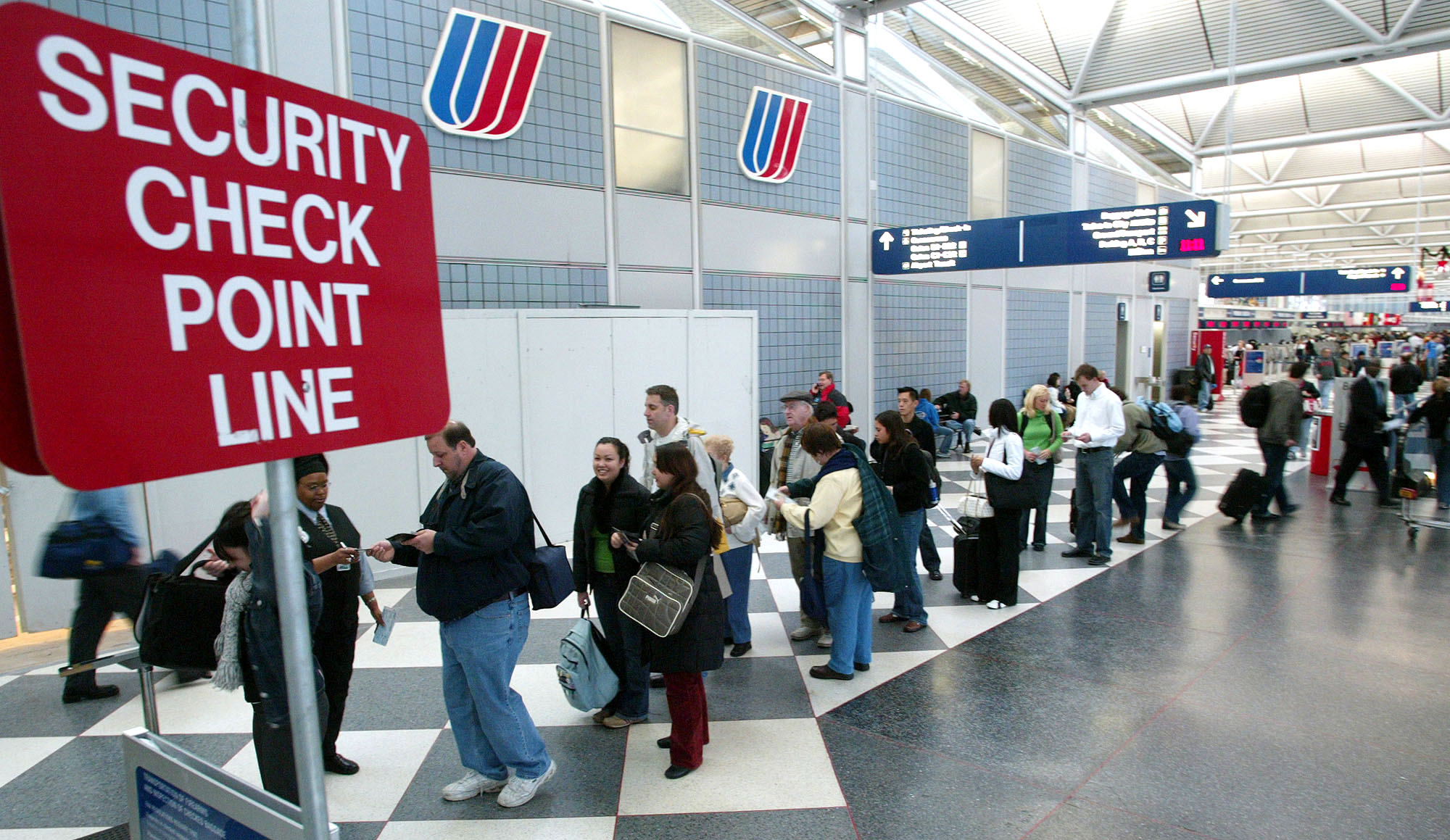 Thanksgiving travelers line up to go though a security check