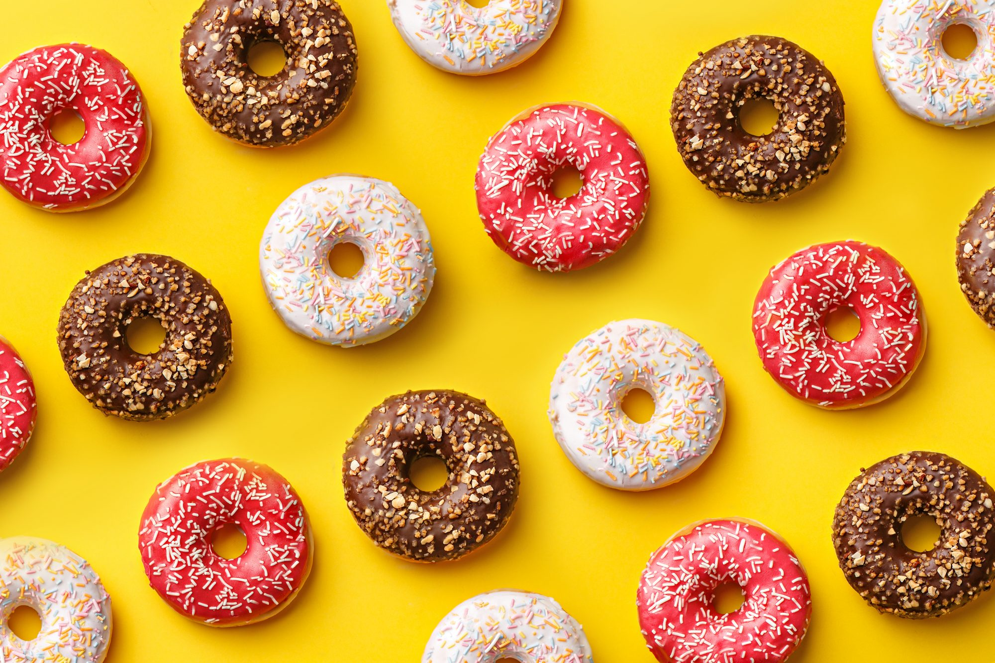 Flat lay donuts pattern on a yellow background. Top view
