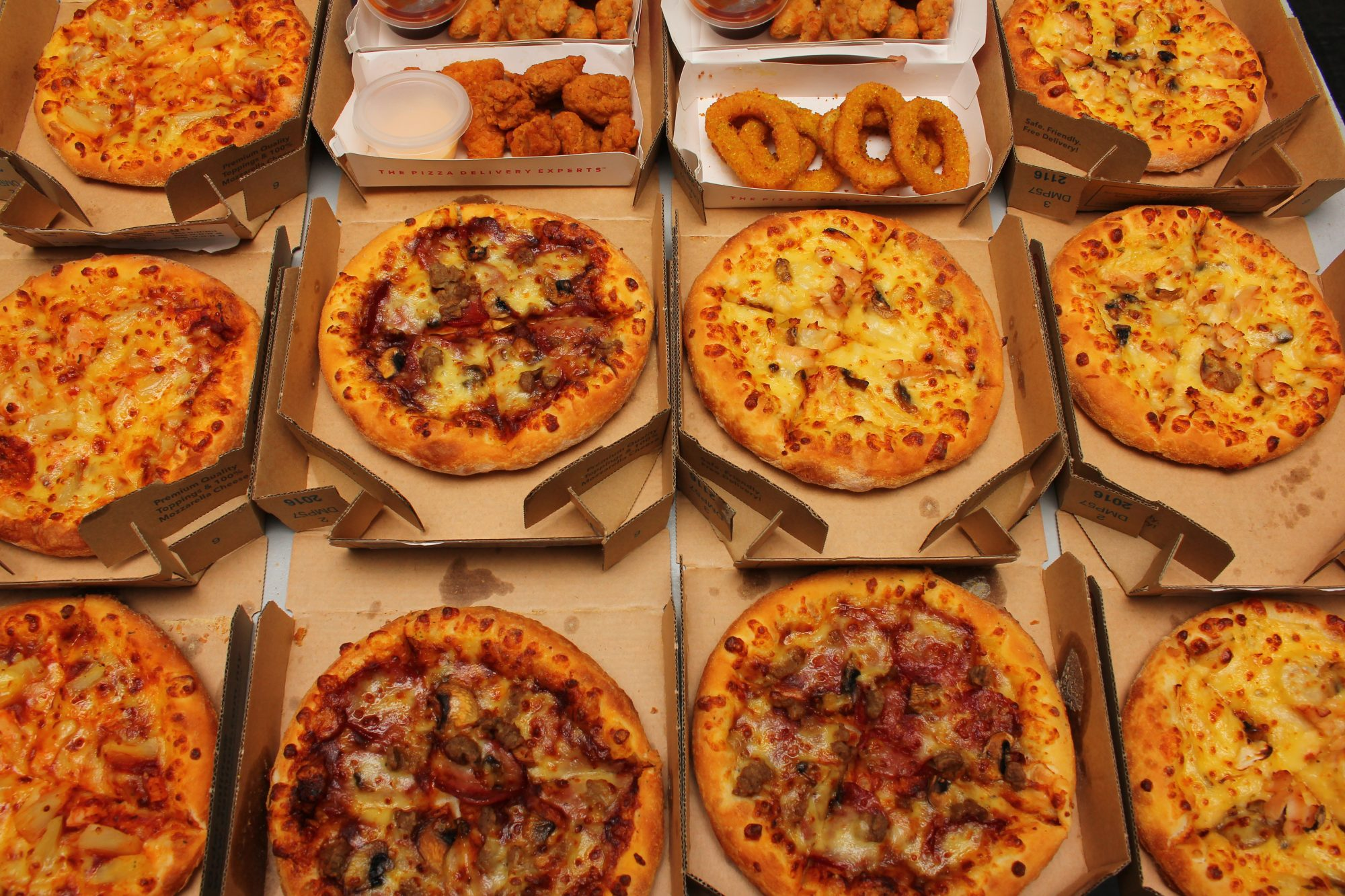High Angle View Of Pizzas In Boxes On Table