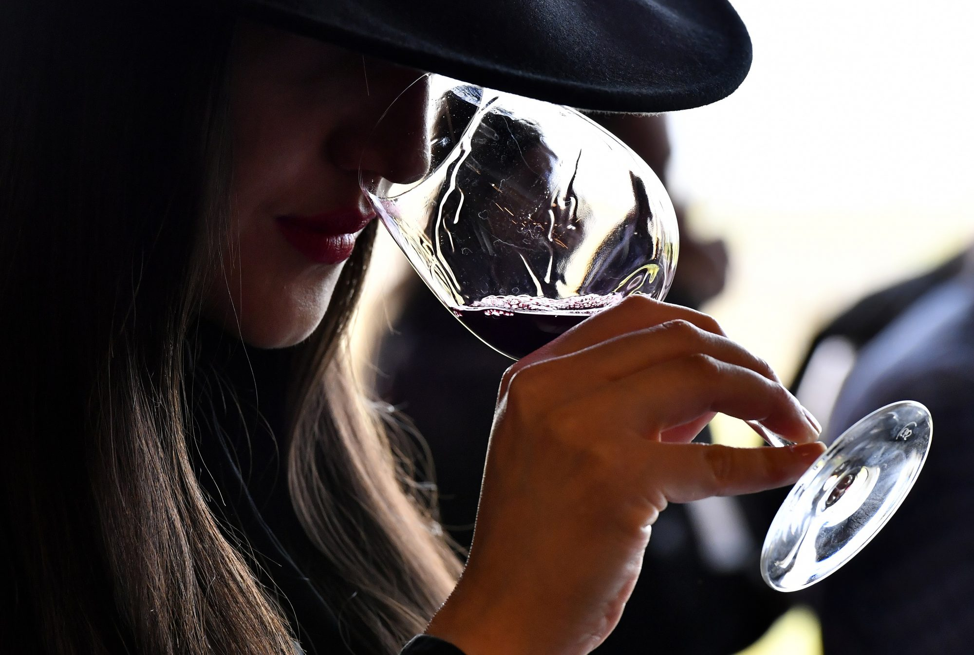 Woman in hat smells glass of red wine