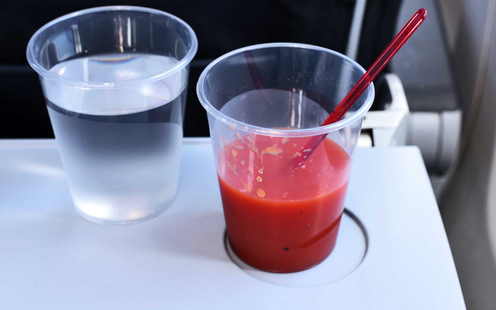 Tomato juice and water glass on a table in an airplane.