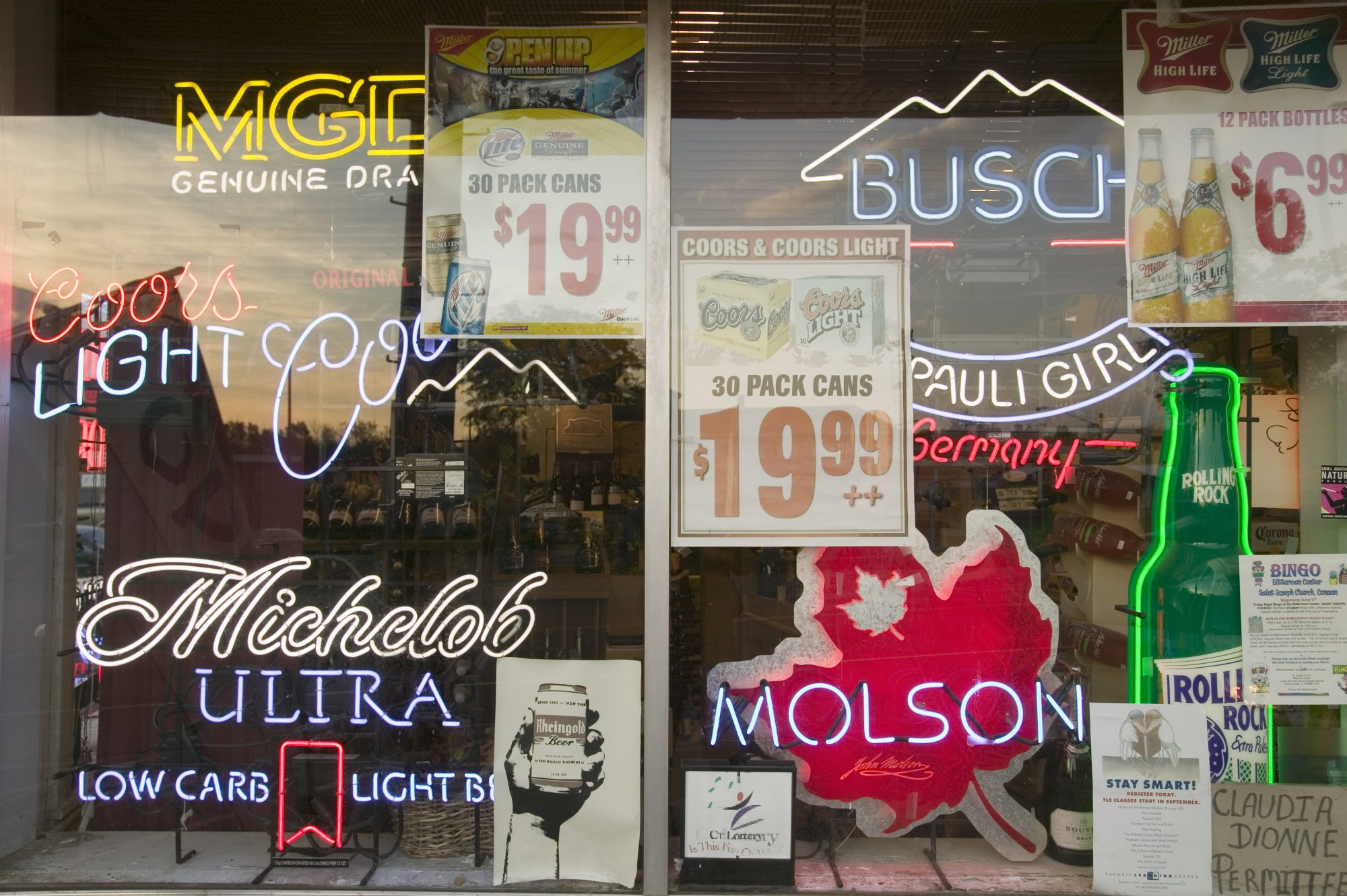 Beer signs in neon in liquor store window of Connecticut
