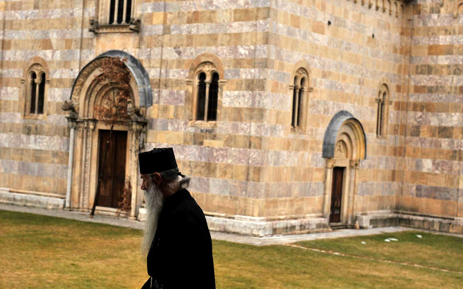 A Serbian Orthodox monk walks outside the Visoki Decani Monastery