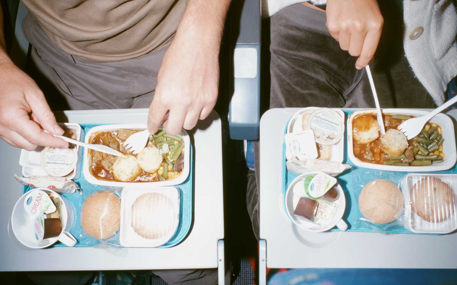Young couple eating meals during a flight