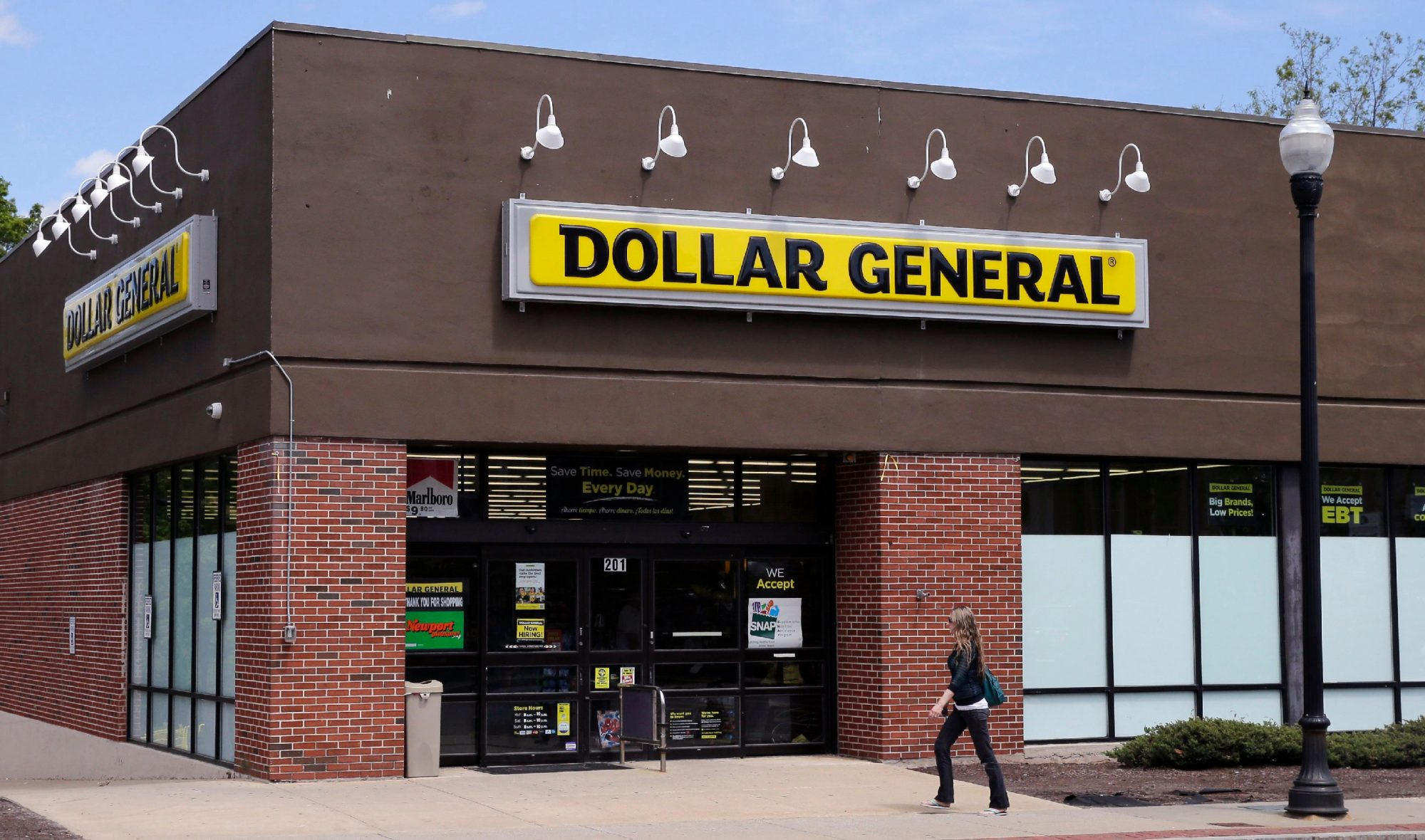 A woman walks past a Dollar General store in Methuen, Mass. On Thursday, May 26, 2016.