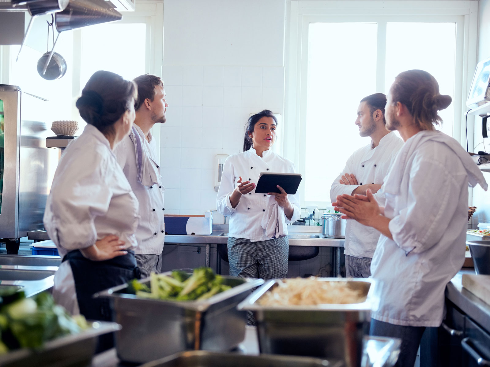 Chefs talking in a restaurant kitchen