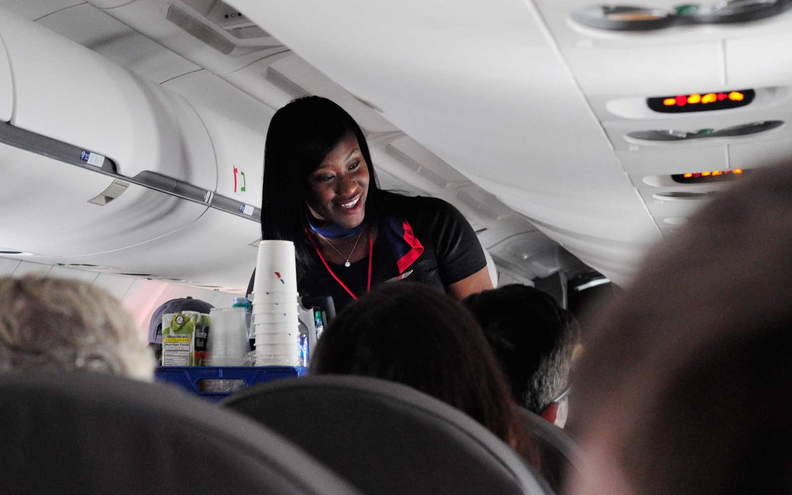 Flight Attendant with beverage cart on flight